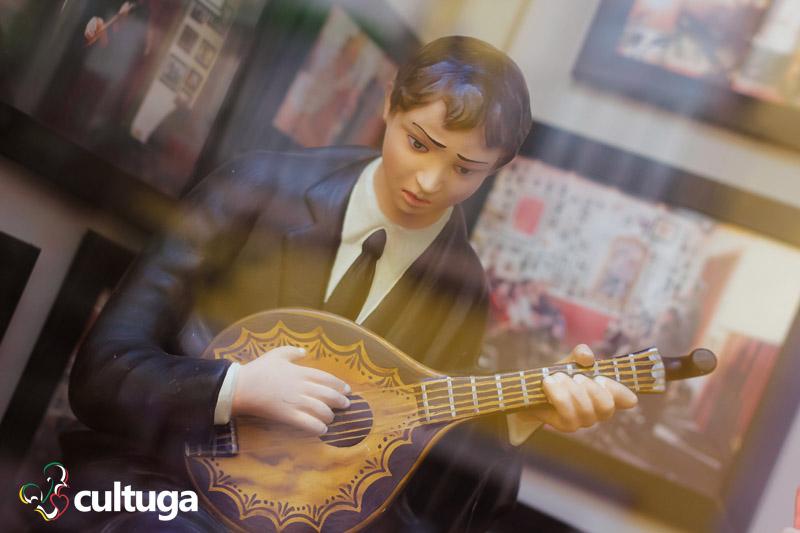 estátua de um homem tocando uma guitarra portuguesa