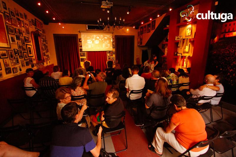 Público aguarda a entrada dos músicos do Fado ao centro em uma sala com muitas fotos e luz baixa
